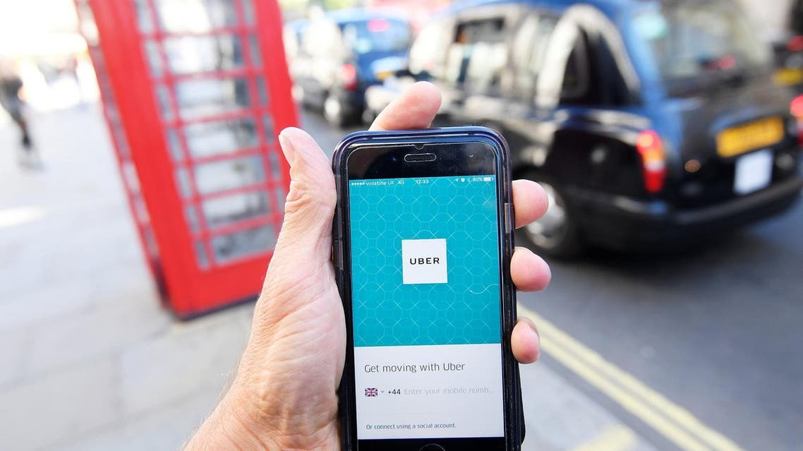 A photo illustration shows a London taxi passing as the Uber app logo is displayed on a mobile telephone in central London September 22, 2017. (Reuters)