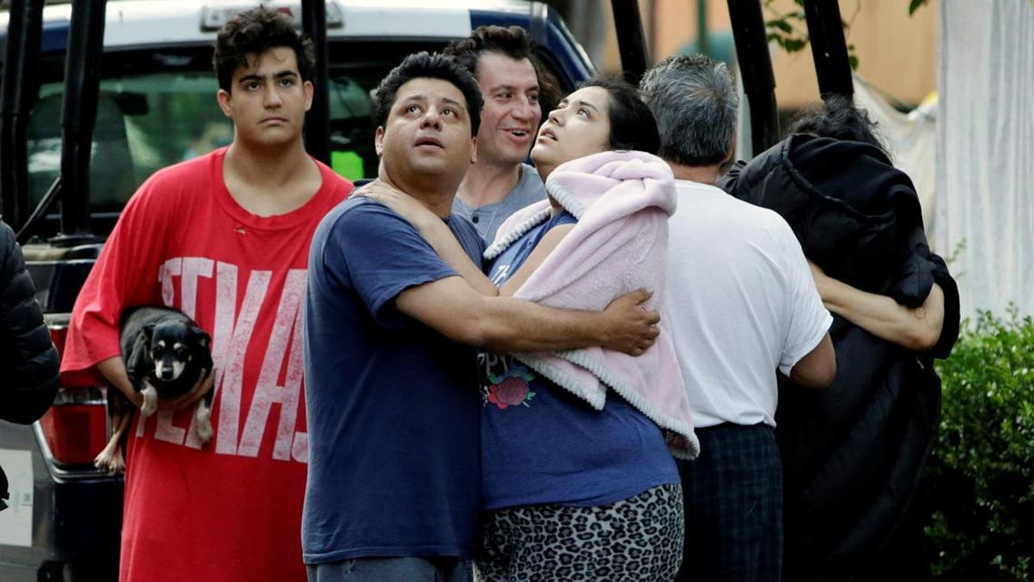 People stand together on a street after a tremor was felt in Mexico City. (Reuters)