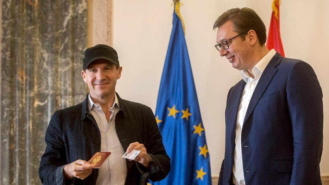 British actor Ralph Fiennes (L) poses after receiving a Serbian passport and ID card from Serbia's President Aleksandar Vucic in Belgrade. (AFP)