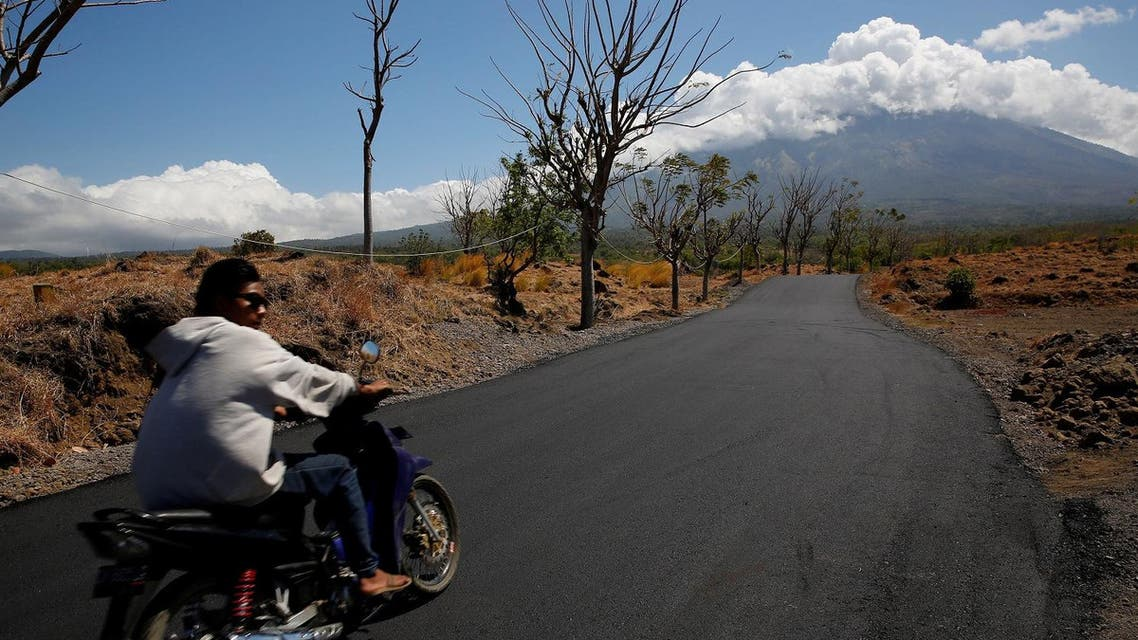 A man rides his motorcycle in the direction of Mount Agung, a volcano on the highest alert level, near Kubu, on the resort island of Bali, Indonesia September 25, 2017. (Reuters)