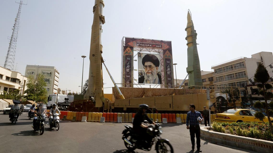 Iranians walk past Sejjil (L) and Qadr-H medium range ballistic missiles next to a portrait of Ayatollah Ali Khamenei on Baharestan square in Tehran on September 25, 2017. (AFP)