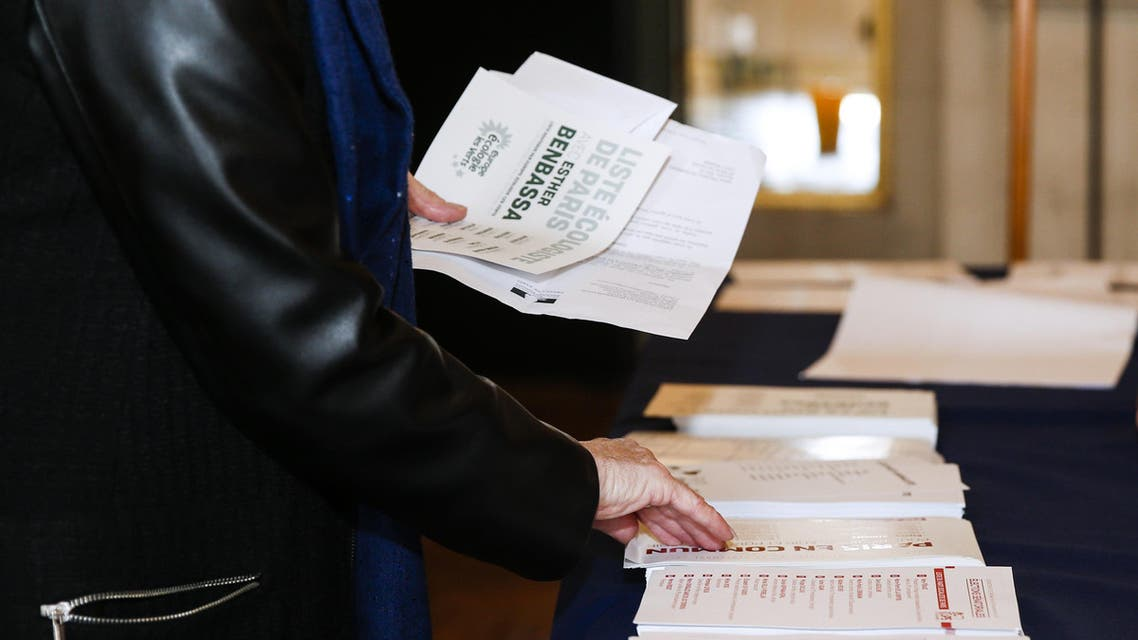 A woman picks up ballot papers as she prepares to vote for the French Senate elections at the Hotel de Ville of Paris on September 24, 2017. Half of the seats in the upper house are up for grabs in the indirect election, in which only elected lawmakers -- parliamentarians, mayors, local councillors -- can vote. GEOFFROY VAN DER HASSELT / AFP