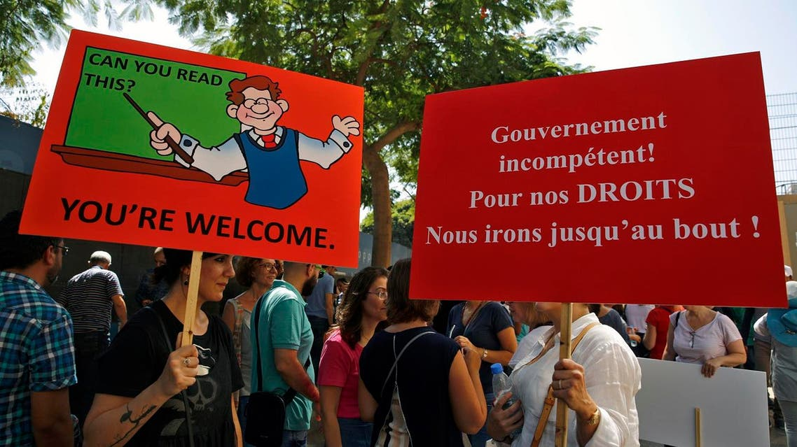 Public sector employees hold placards during a protest in front of the government building in downtown Beirut, Lebanon, Tuesday, Sept. 26, 2017. Lebanon's civil servants are on strike to pressure the government to pay them recently approved wage hikes amid a new crisis over how to finance the wages bill, estimated at $800 million. (AP Photo/Bilal Hussein)