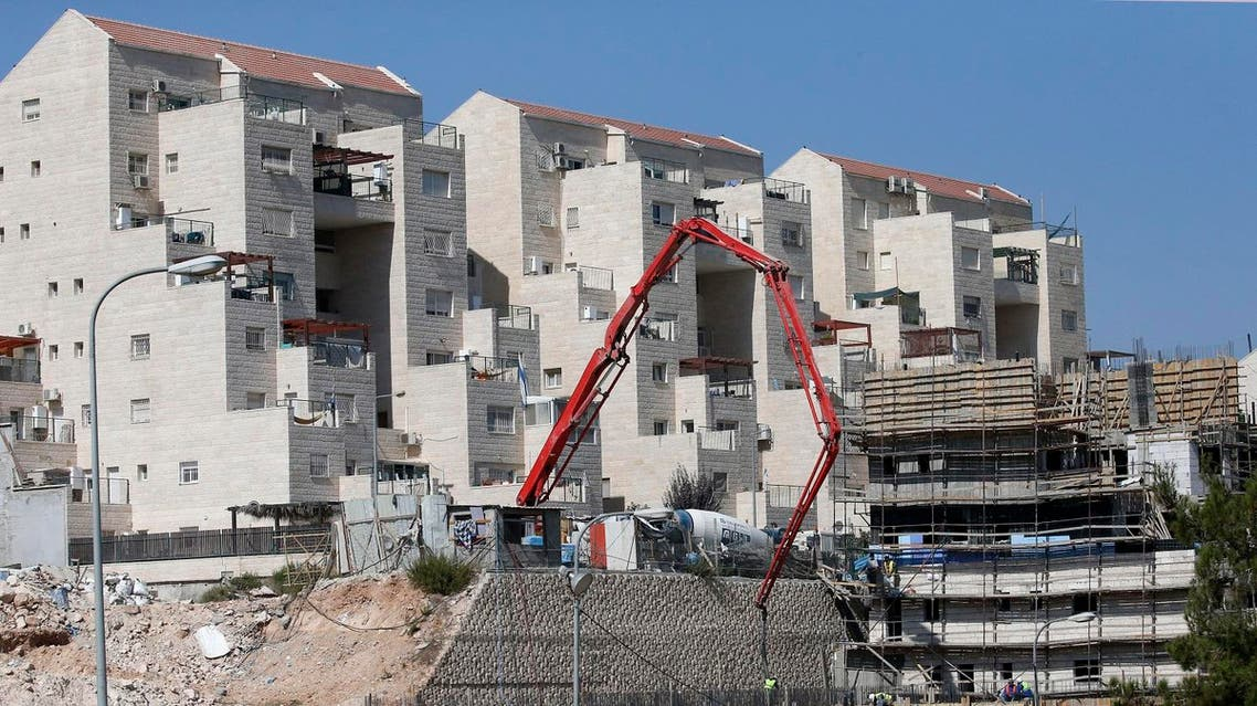 Construction workers build new houses in the Israeli settlment of Kiryat Arba, east the West Bank town of Hebron, August 24, 2017. (AFP)