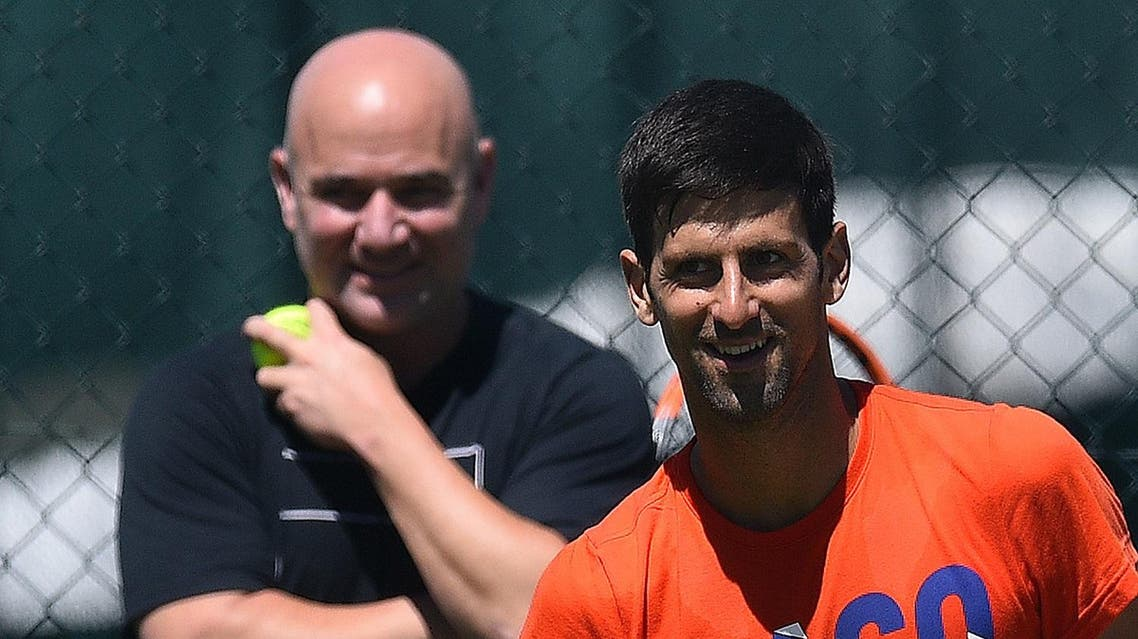 US coach Andre Agassi (L) watches Serbia's Novak Djokovic as he attends a practice session at The All England Tennis Club in Wimbledon, southwest London, on July 2, 2017, on the eve of the start of the 2017 Wimbledon Championships tennis tournament. (AFP)