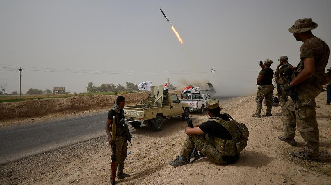 Shi'ite Popular Mobilization Units (PMU) with Iraqi rapid response members fire a missile against ISIS on the outskirts of Shirqat. (Reuters)