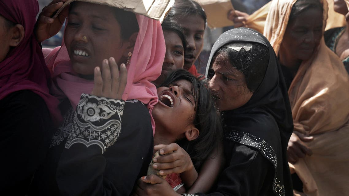 A Rohingya refugee girl reacts as people wait to receive aid in Cox's Bazar, Bangladesh, September 25, 2017. REUTERS/Cathal McNaughton