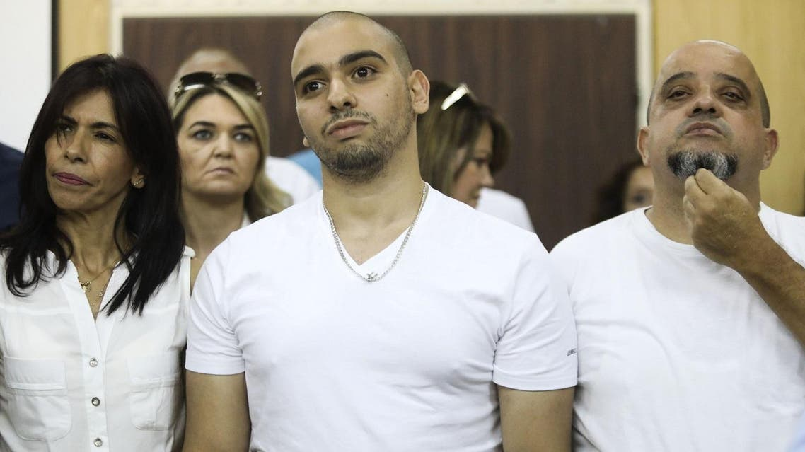 (FILES) This file photo taken on July 30, 2017 shows Israeli soldier Elor Azaria (C), who shot dead a wounded Palestinian assailant in March 2016, standing next to his mother Oshra (L) and father Charlie during a hearing at a military court in Tel Aviv. Israel's military chief of staff on September 27, 2017, reduced the sentence of Azaria convicted of manslaughter for shooting dead a prone Palestinian assailant by four months, with the case having deeply divided the country. (AFP)