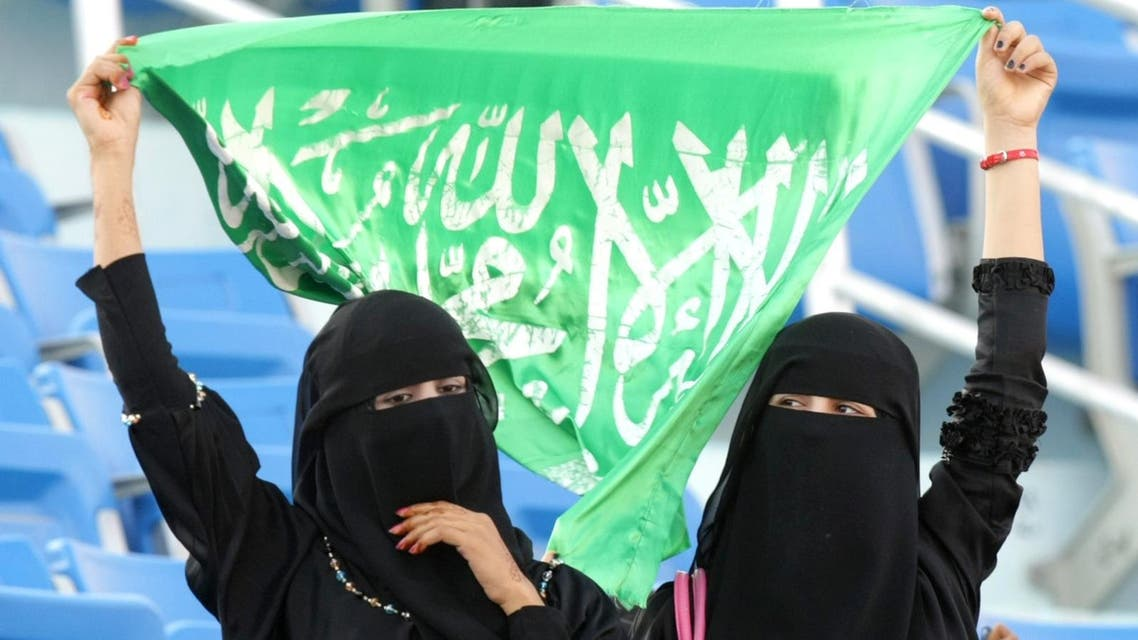 Saudi women hold up their national flag as they watch the official opening ceremony of the Gulf Cup at the 22 May Stadium in the southern city of Aden on November 22, 2010 as Yemen gets ready to host the football tournament amid tight security. AFP PHOTO/KARIM SAHIB