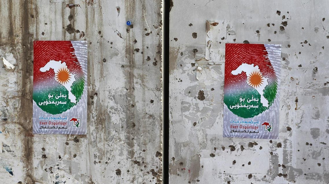 Posters encouraging people to vote in the upcoming independence referendum for the Kurdistan region are seen on a bullet-riddled wall in the Iraqi city of Kirkuk on September 24, 2017. Iraqi Kurds are preparing to vote in a referendum set for September 25 on independence for their autonomous northern region, despite warnings within the country and from neighbours Iran and Turkey. AFP