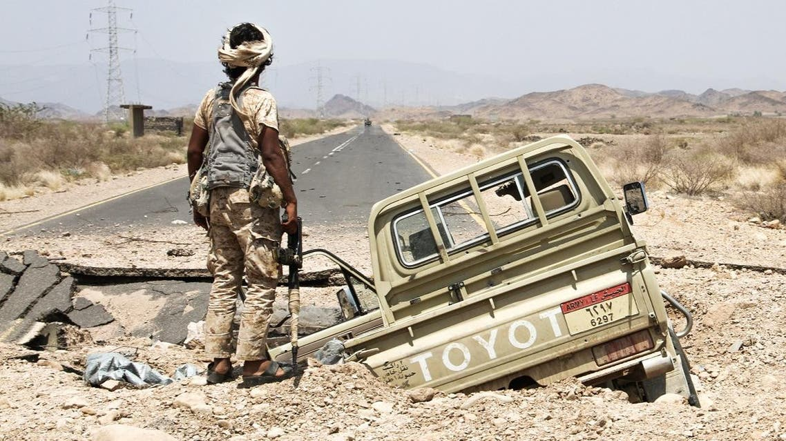 A Yemeni fighter loyal to the Saudi-backed Yemeni president stands next to an army Toyota pickup truck as it lies in hole on the road leading to Khaled Ibn Al-Walid base, 30 kilometres (20 miles) east of the government-held Red Sea port town of Mokha, on April 15, 2017. (AFP)