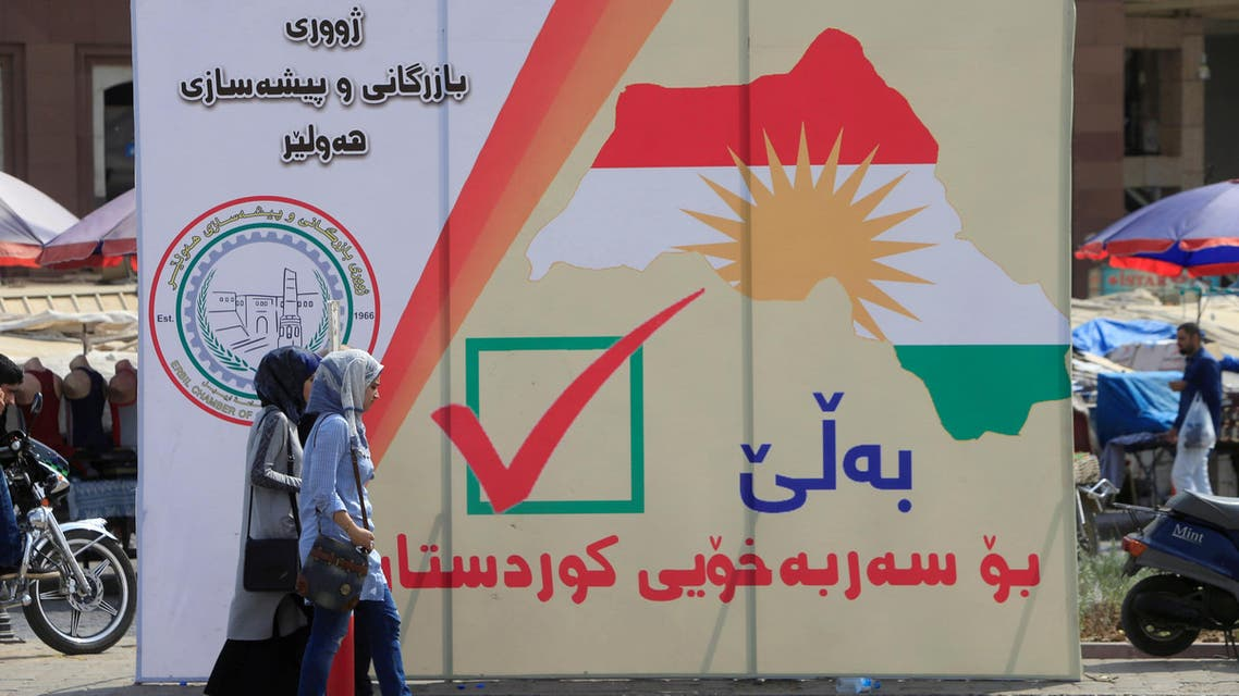 Iraqi women walk on the street, near banners supporting the referendum for independence for Kurdistan in Erbil, Iraq September 21, 2017. REUTERS/Alaa Al-Marjani