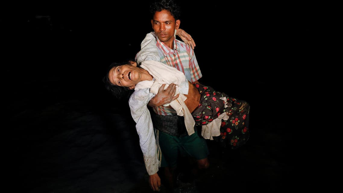 Nobi Hossain wades through the water carrying his elderly relative Sona Banu under the cover of darkness from Myanmar to Cox's Bazar in Bangladesh, on September 27, 2017. (Reuters)
