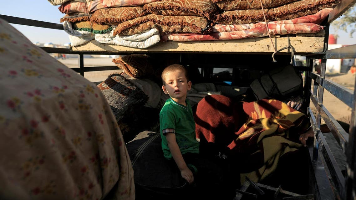 A boy who fled Deir Ezzor sits on a truck with his family belongings at a camp in Ain Issa, north of Raqqa, Syria August 12, 2017. (Reuters)