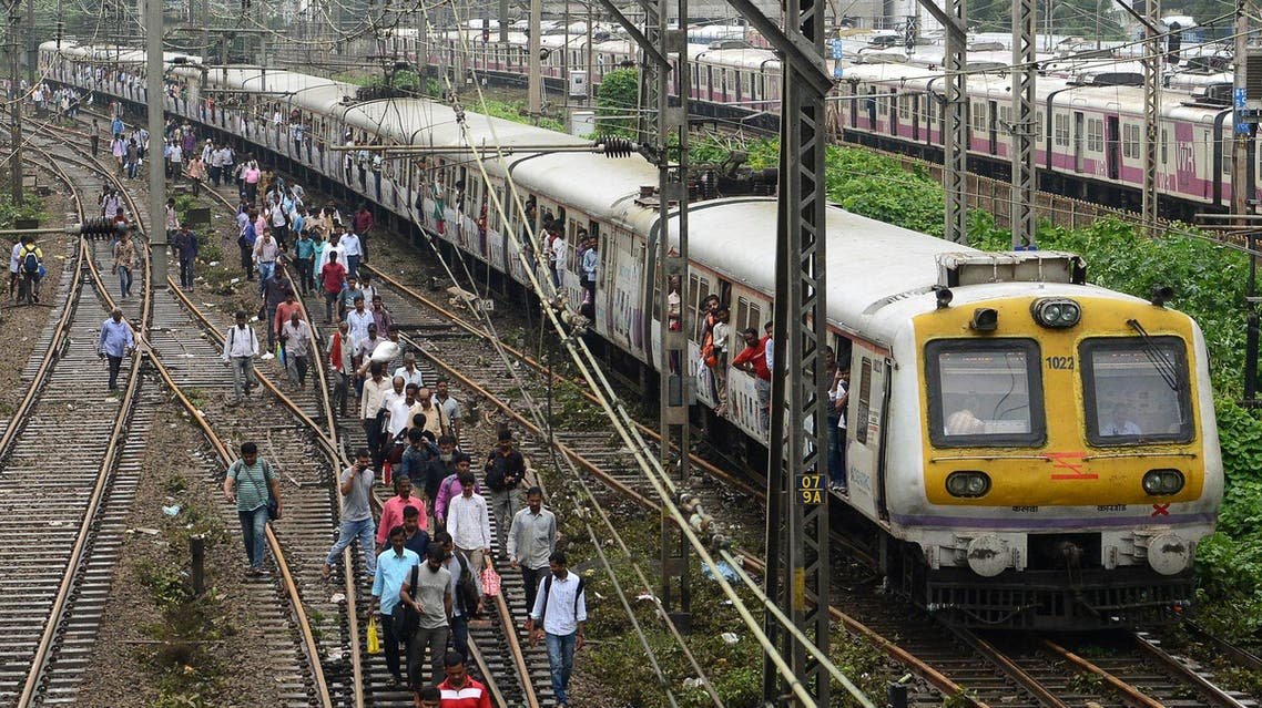 Indian commuters walk on railway tracks as train services slowly resume in Mumbai on August 30, 2017, after heavy rains brought major flooding to the coastal city. (AFP)