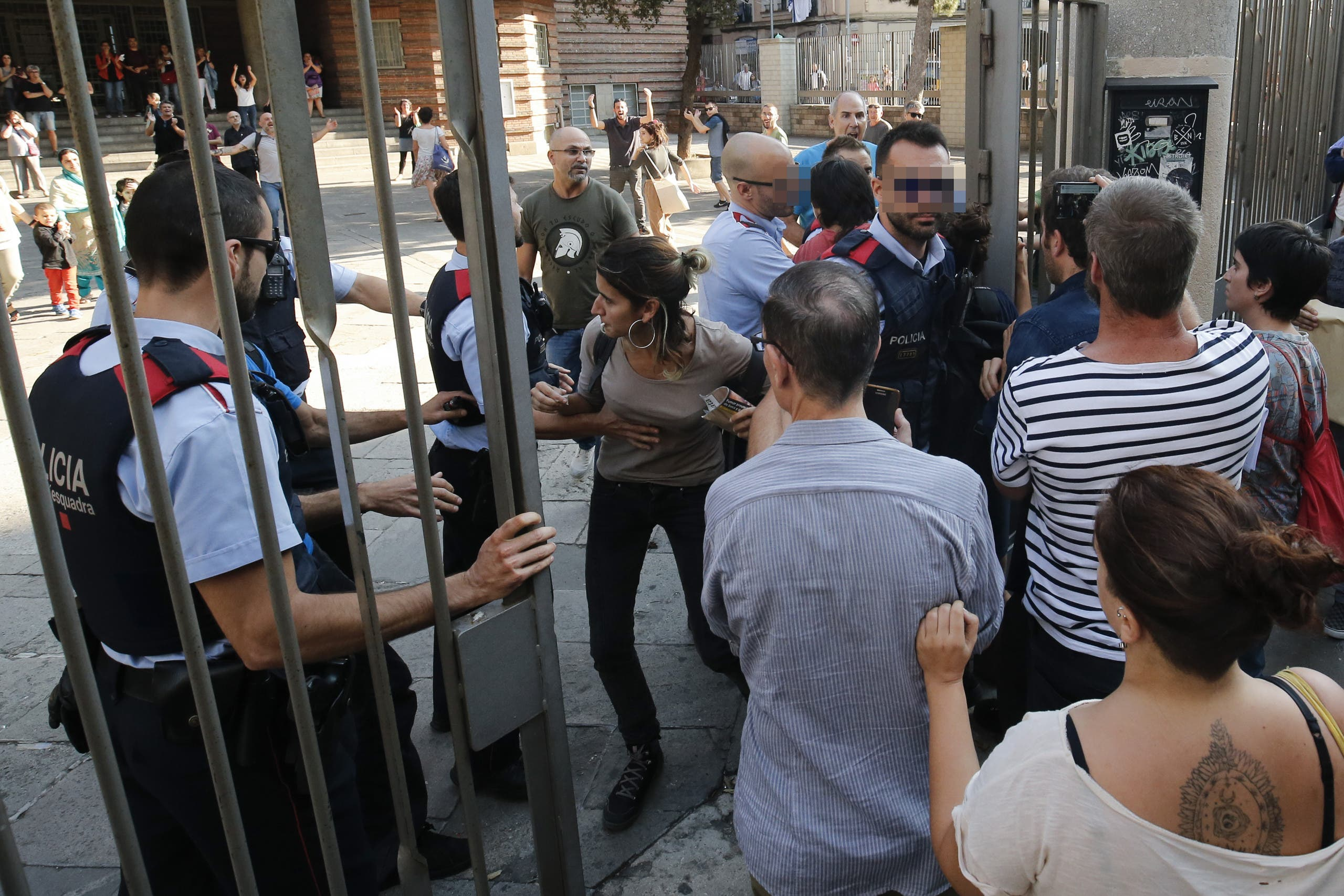 Catalan police officers 'Mossos d'Esquadra' try stop pro-referendum people from going into 'Escola Collaso i Gil' school on September 29, 2017 in Barcelona. (AFP)