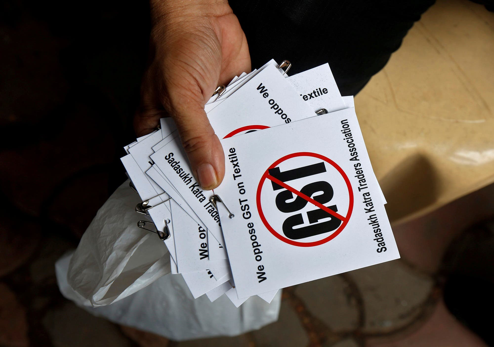A cloth merchant holds message papers to distribute during a protest against the Goods and Services Tax (GST) on textiles in Kolkata, India, June 30, 2017. (Reuters)