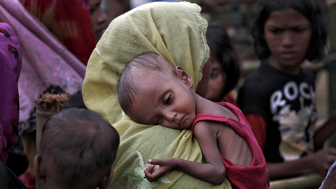 A woman carries an ill Rohingya refugee child through a camp in Cox's Bazar, Bangladesh, September 28, 2017. REUTERS/Cathal McNaughton