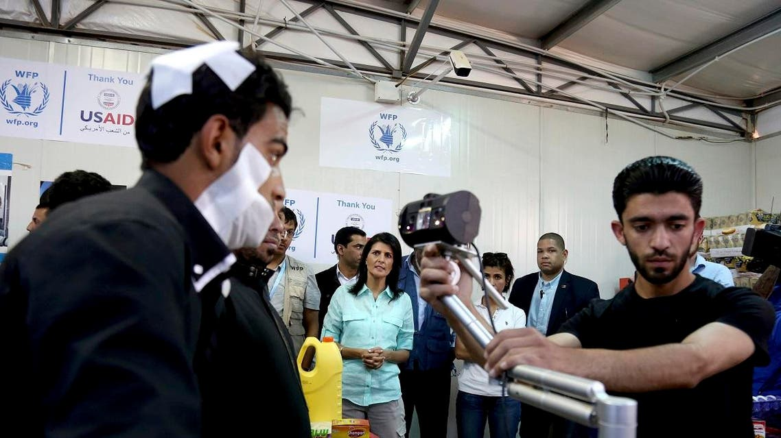 US Ambassador to the United Nations Nikki Haley looks on as a bandaged Syrian refugee has his iris scanned at a supermarket in Zaatari Refugee Camp, Jordan. (File photo: AP)