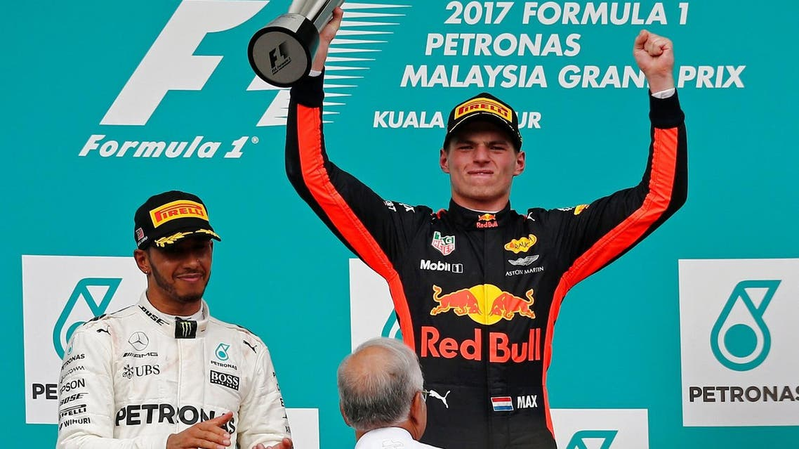 Redbull's Max Verstappen celebrates winning the race beside Mercedes' Lewis Hamilton and Malaysian Prime Minister Najib Razak at the Malaysia Grand Prix in Sepang on October 1, 2017. (Reuters)
