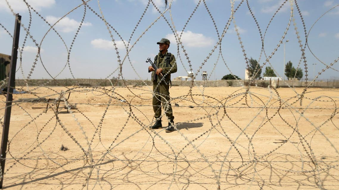 A member of the Palestinian security forces stands guard as men set up a barbed wire on the border with Egypt, in Rafah in the southern Gaza Strip, August 24, 2017. (Reuters)