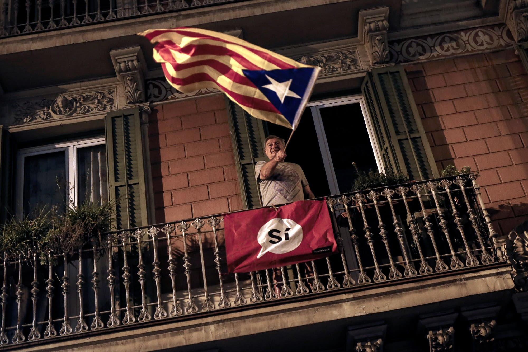 A man waves an 'Estelada' (Pro-independence Catalan flag) from a balcony after the closing of the La Fontana youth center polling station, on October 1, 2017 in Barcelona. (AFP)