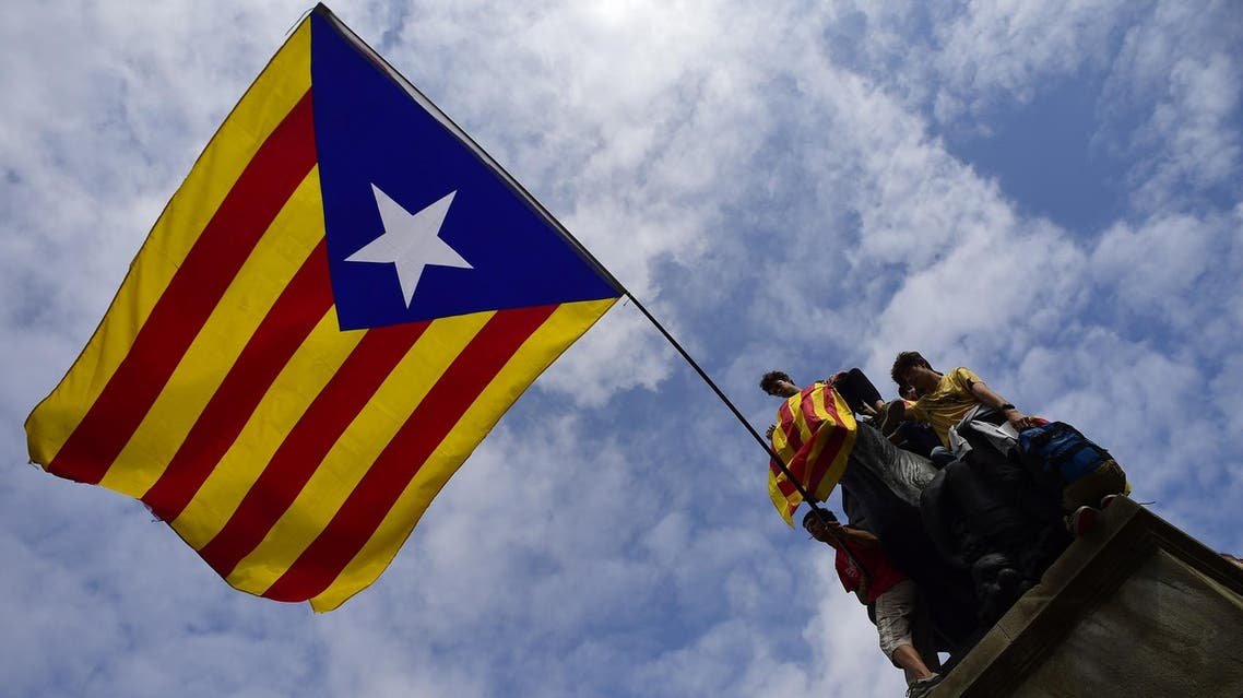 Protesters wave a giant Catalan pro-independence 'Estelada' flag atop a sculpture during a demonstration in Barcelona on October 2, 2017. (AFP)