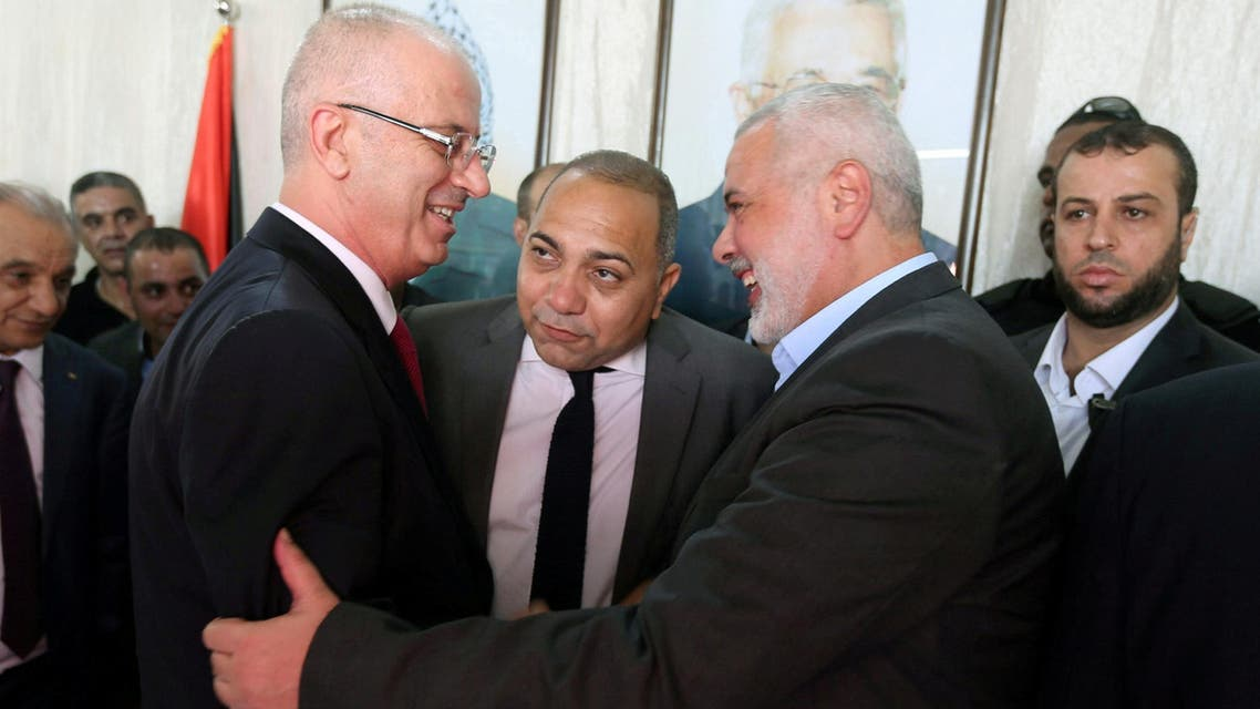 Palestinian Prime Minister Rami Hamdallah (L) shakes hands with Hamas Chief Ismail Haniyeh in Gaza City October 2, 2017. REUTERS/Ibraheem Abu Mustafa TPX IMAGES OF THE DAY