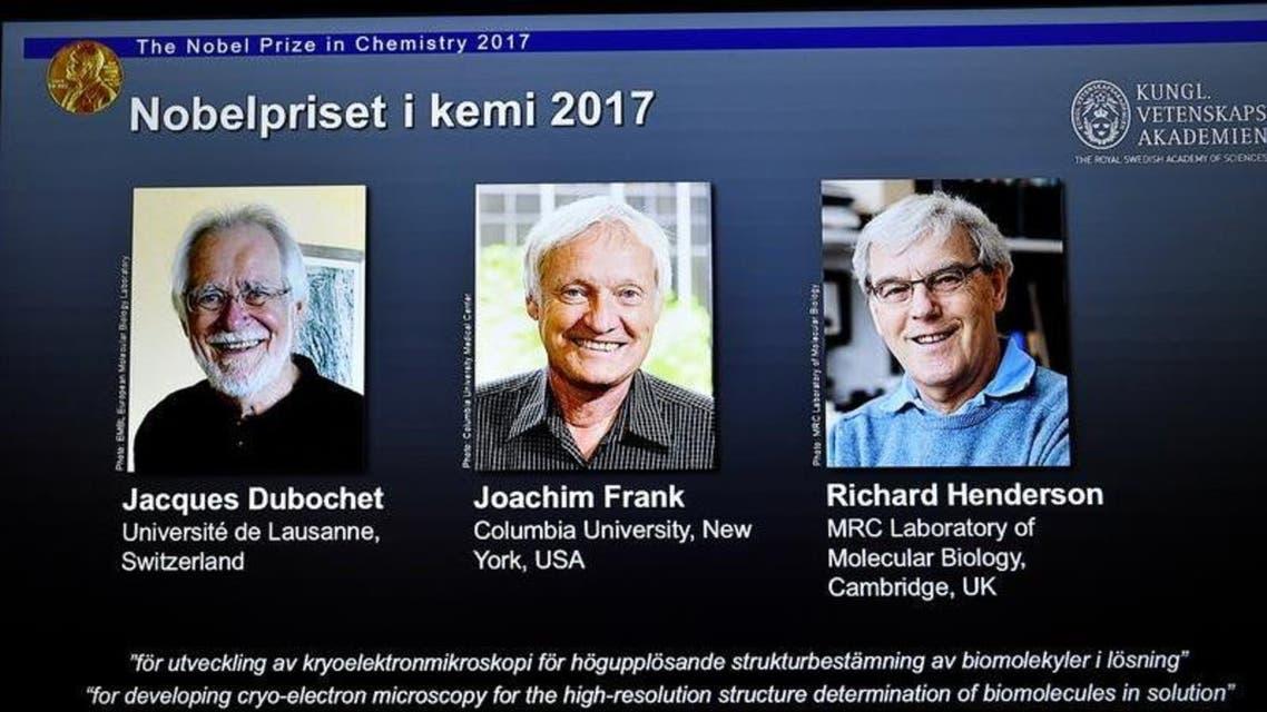 صور وأسماء العلماء جاك دوبوشيه ويواكيم فرانك وريتشارد هندرسون معروضة خلال إعلان فوزهم بجائزة نوبل في الكيمياء لعام 2017 في ستوكهولم