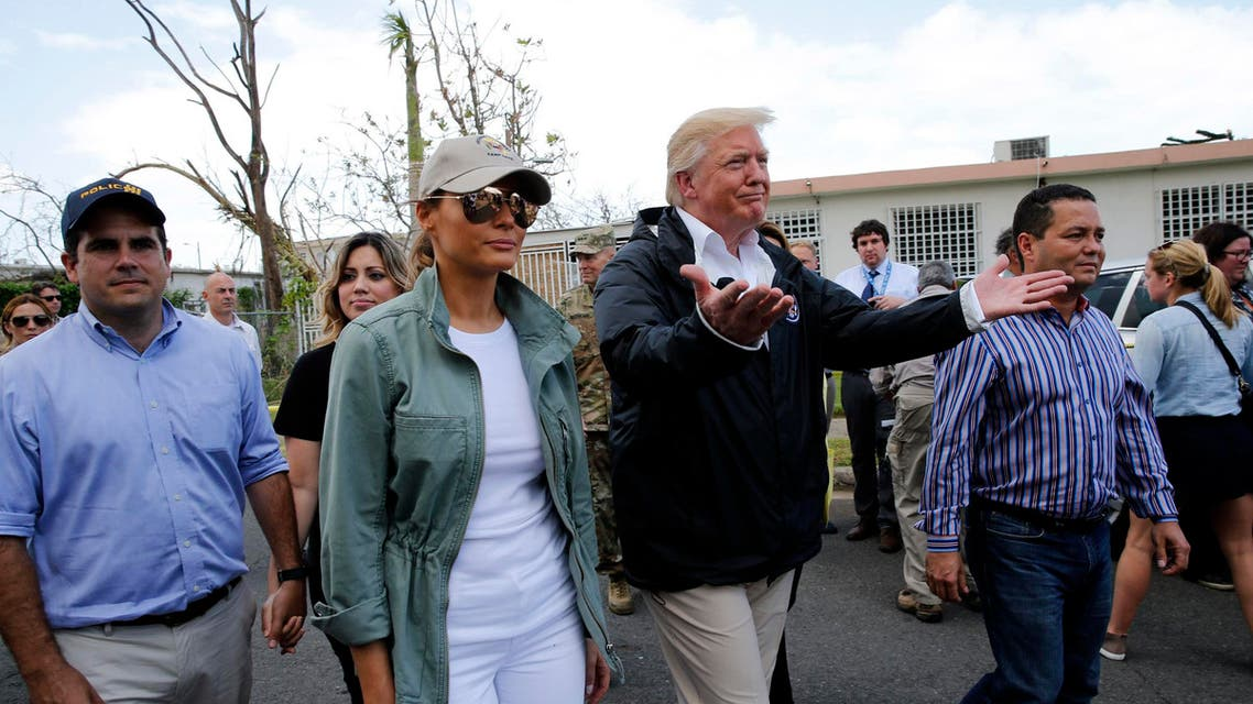 U.S. President Donald Trump and first lady Melania Trump walk through a neighborhood damaged by Hurricane Maria in Guaynabo, Puerto Rico, U.S., October 3, 2017. REUTERS/Jonathan Ernst