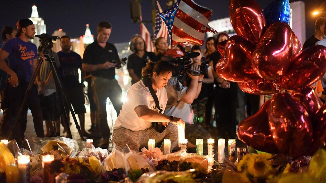 A woman lights a candle at a makeshift memorial near the Mandalay Hotel on the Las Vegas Strip, in Las Vegas, Nevada on October 3, 2017, after a gunman killed 58 people and wounded more than 500 others. (AFP)