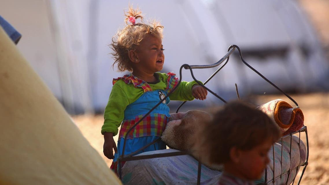 A Syrian child from the eastern city of Deir Ezzor, who was displaced by the war against the Islamic State (IS) group, cries as she stands next to a makeshift bed outside the Ain Issa camp on September 23, 2017. (AFP)