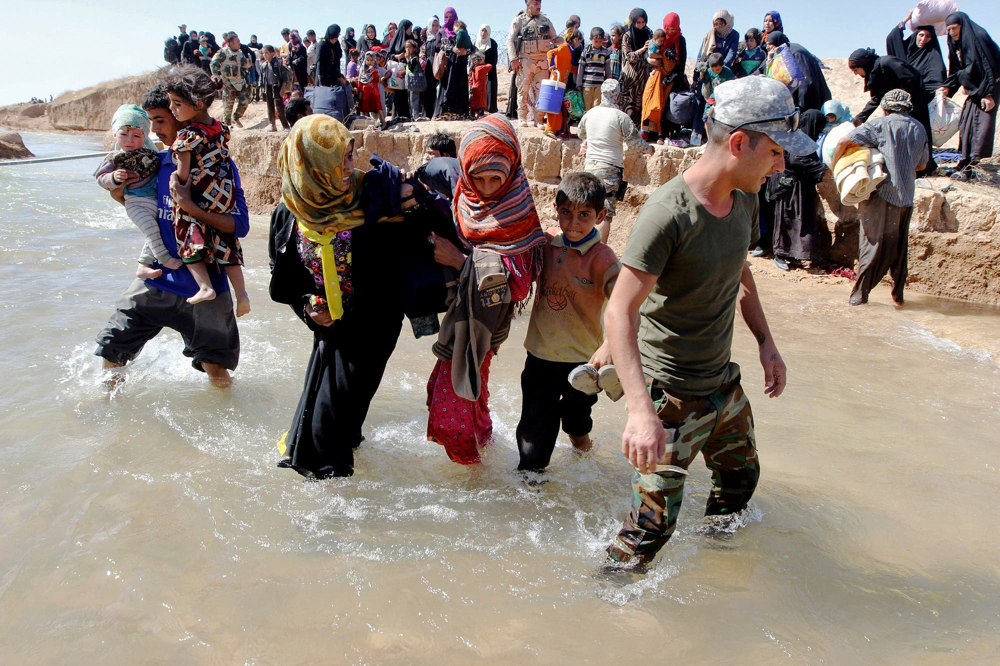 Displaced people, who fled from their homes in Hawija, cross the water to reach the other bank to be transported to camps for displaced people, in southwest of Kirkuk, Iraq, October 4, 2017. (Reuters)