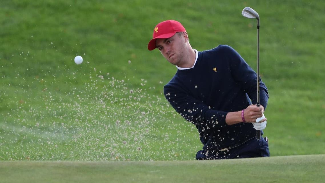 Justin Thomas hits a shot out of the sand on the fourth hole during the third round foursomes matches of The President's Cup golf tournament at Liberty National Golf Course. (Reuters)
