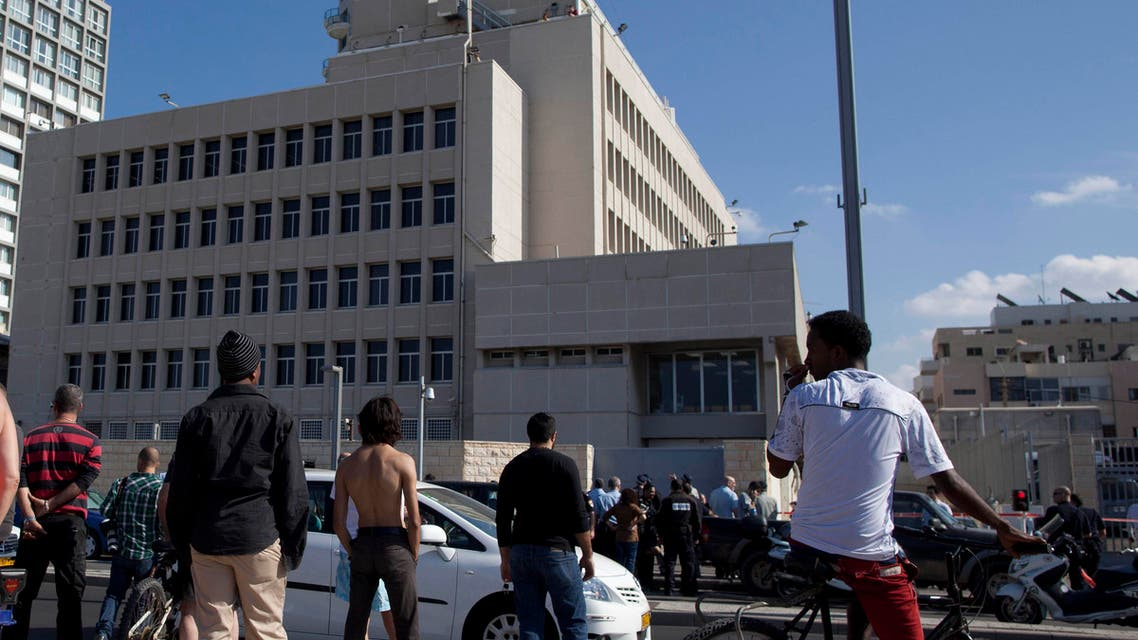 Israelis stand near the scene where a man attacked a security guard at the U.S. embassy, seen in background, in Tel Aviv, Israel, Tuesday, Nov. 20, 2012. ap