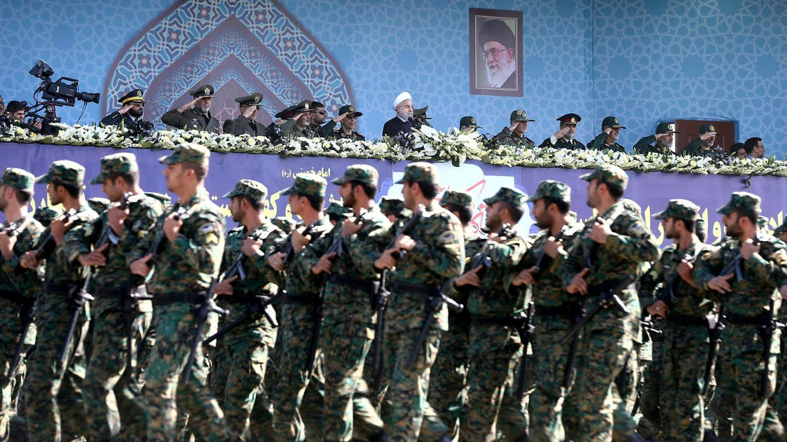 Iran's President Hassan Rouhani, top center, reviews army troops marching during the 37th anniversary of Iraq's 1980 invasion of Iran, in front of the shrine of the late revolutionary founder, Ayatollah Khomeini, just outside Tehran, Iran, Friday, Sept. 22, 2017. AP