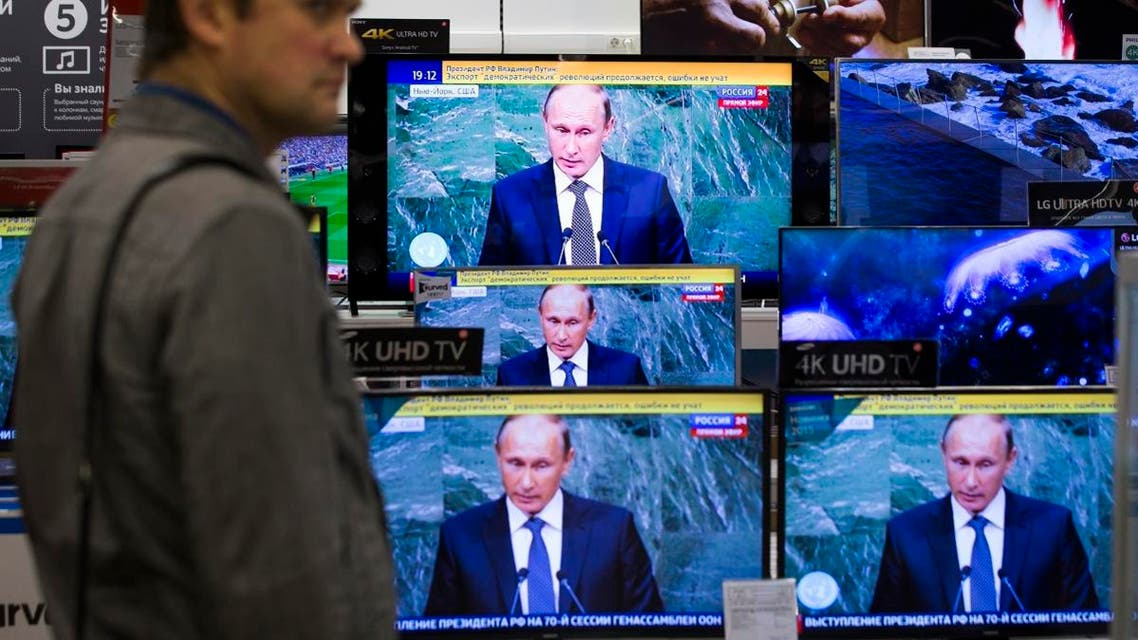 A man looks at television screens in an electronics shop as Russian President President Vladimir Putin addresses the 70th session of the United Nations General Assembly, Moscow, Russia, Monday, Sept. 28, 2015. (AP)