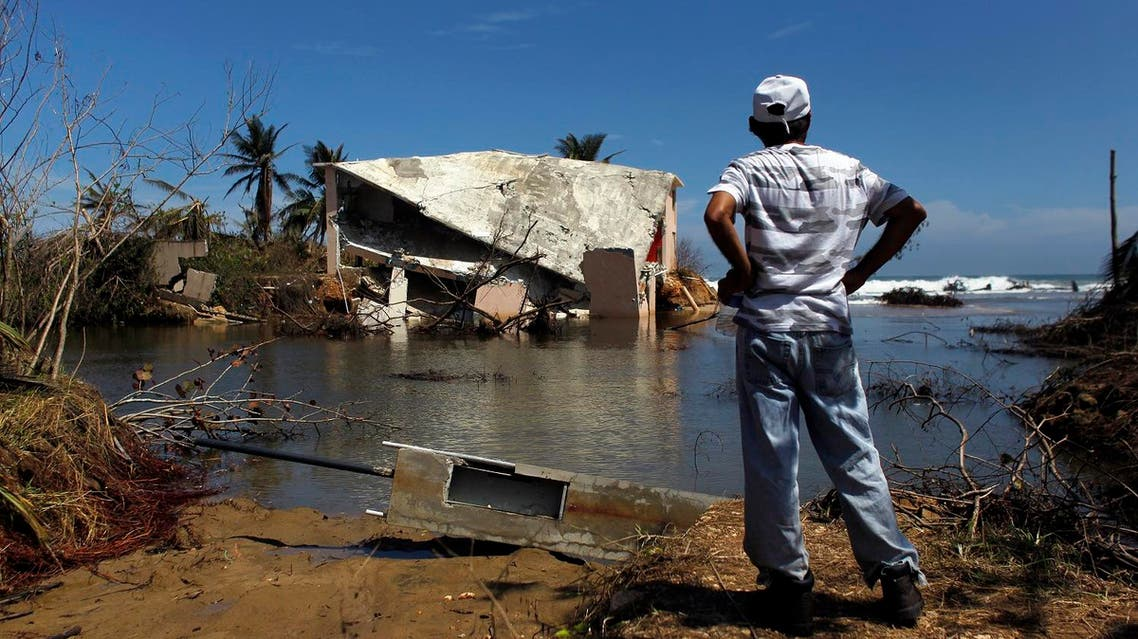 A man surveys a house that was washed away by heavy surf during the passing of Hurricane Maria in Manati, Puerto Rico, on October 6, 2017. (AFP)