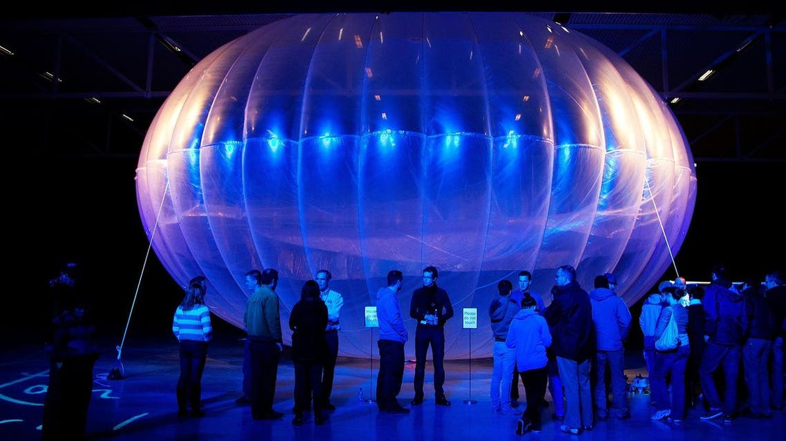 Visitors stand next to a high altitude WiFi internet hub, a Google Project Loon balloon, on display at the Airforce Museum in Christchurch. (AFP)