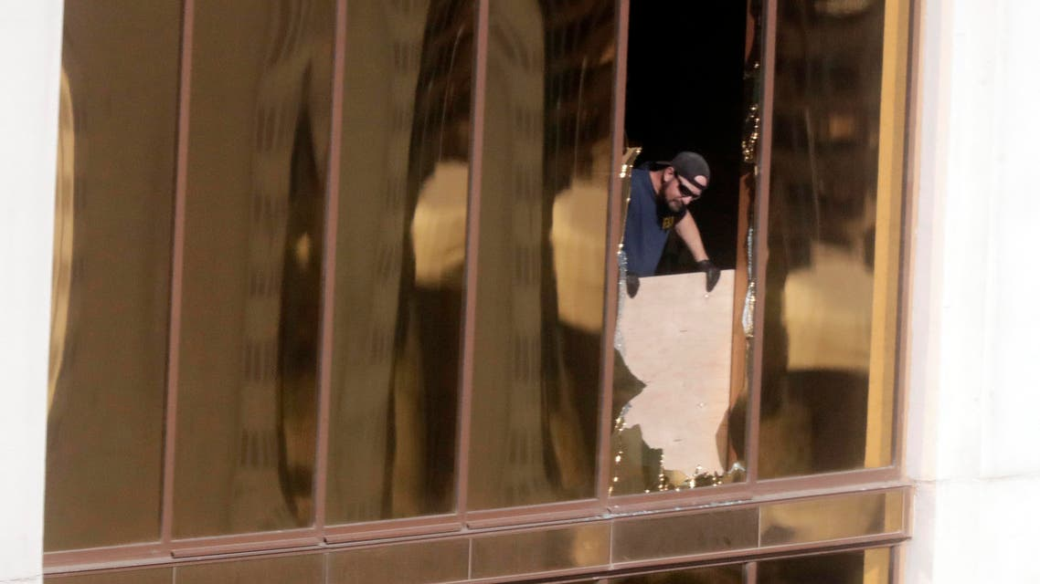 Agents from the FBI use binoculars from the broken window where a gunman opened fire at the Mandalay Bay hotel, Wednesday, Oct. 4, 2017, in Las Vegas. (AP)