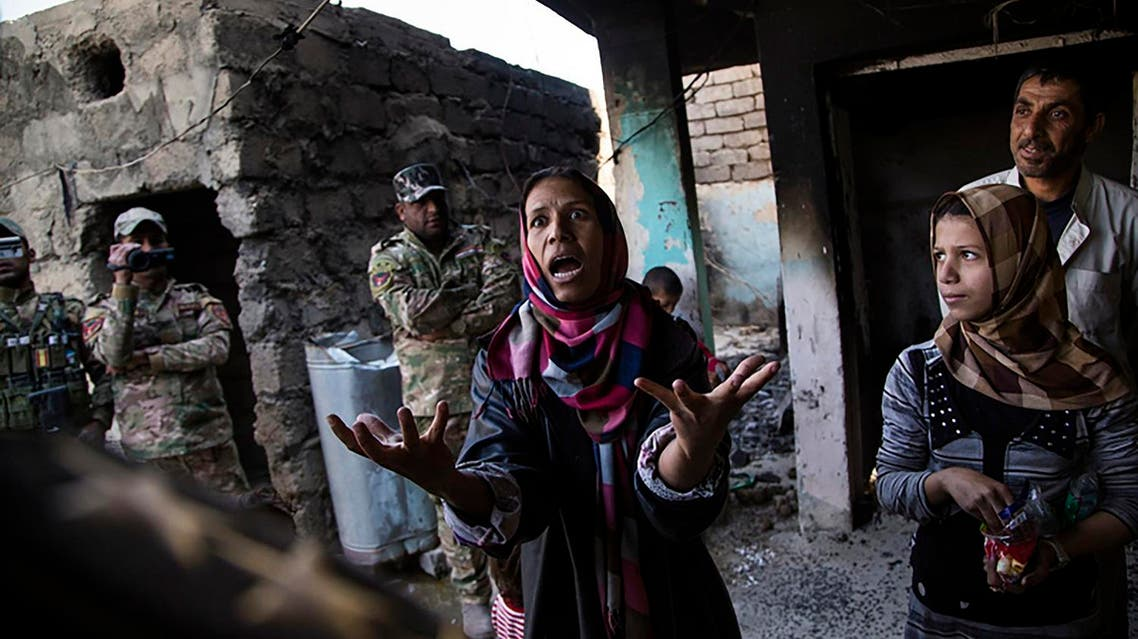 """A photo handout on October 7, 2017 by the Bayeux-Calvados Awards for war correspondents, and taken on November 7, 2016 by Iraqi photographer Ali Arkady, from the VII Photo agency, as part of his photographic coverage of the Mosul battle entitled """"Kissing Death"""", shows a woman in fear speaking with an ERD intelligence officer, after her house was bombed by Iraqi air strikes and her brother kidnapped by ISIS, in Qabr al-Abd village, near Mosul. Ali Arkady received on October 7, 2017 the Photo Prize award of the 2017 Bayeux-Calvados Awards for war correspondents, for his work """"Kissing Death"""". AFP"""