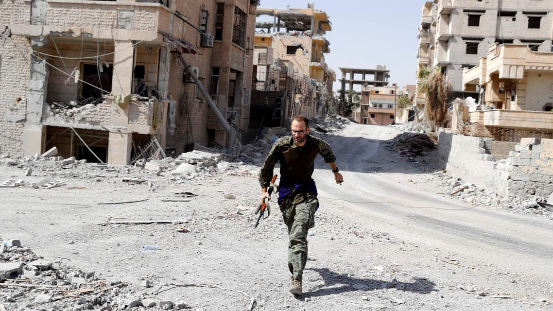 A British volunteer fighter of Syrian Democratic Forces runs for cover to avoid sniper fire of Islamic State militants, at the frontline in Raqqa, Syria October 7, 2017. REUTERS/