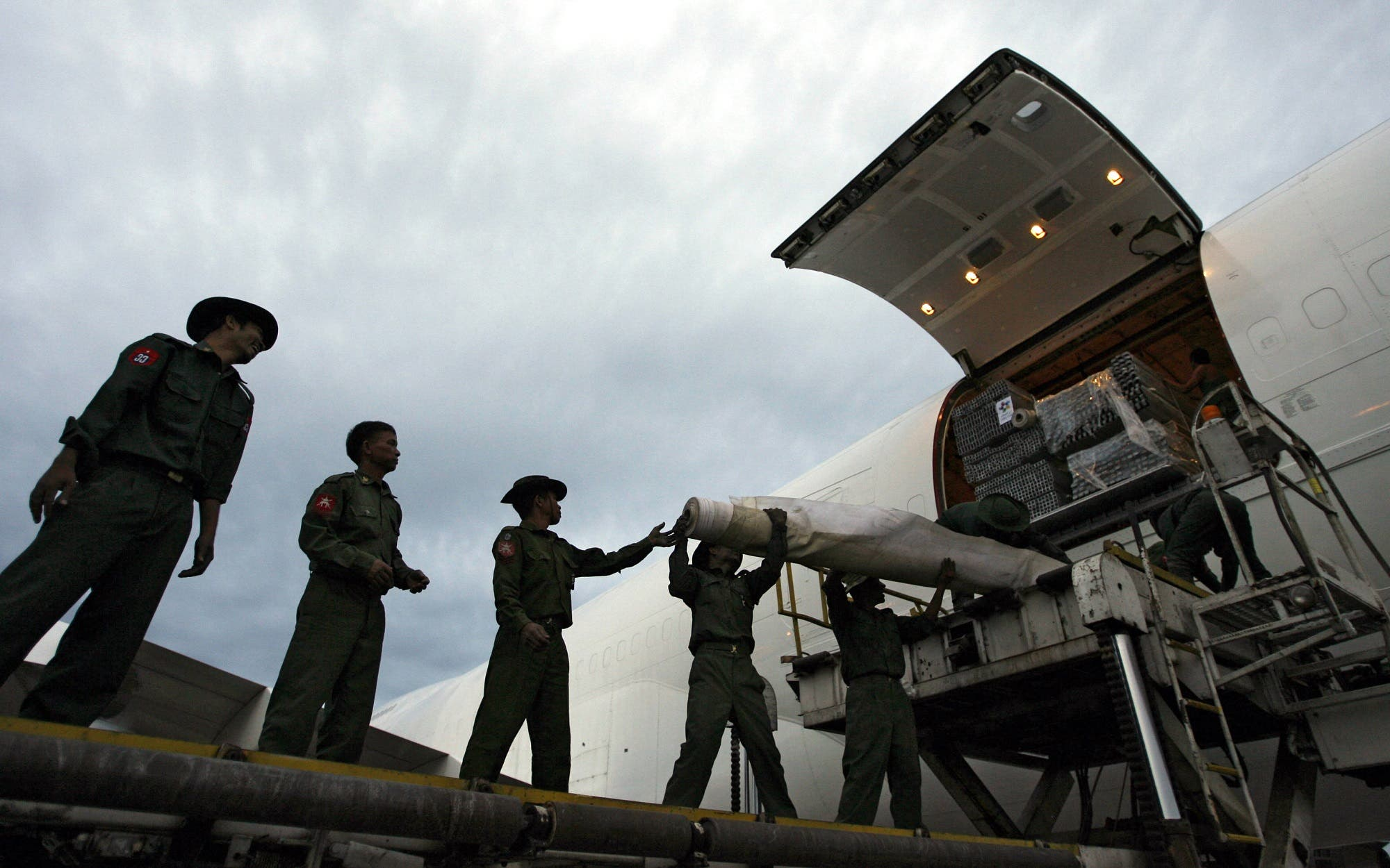 "Myanmar soldiers and ""Dubai Cares"" personnel off-load aid from Dubai at Yangon International Airport for victims of Cyclone Nargis early on May 12, 2008. (AFP)"