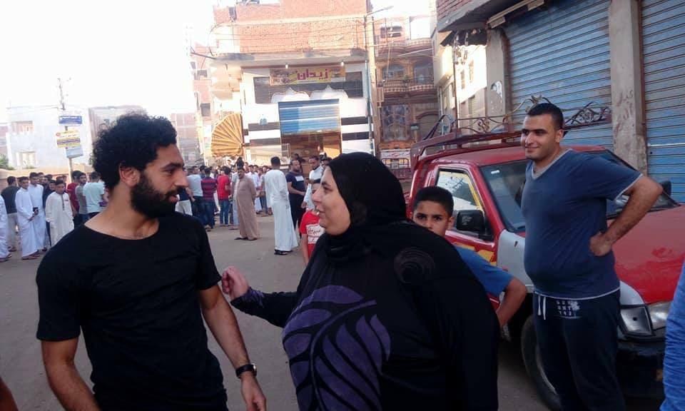 مع سيدة من أبناء قريته بعد صلاه عيد الفطر الماضي