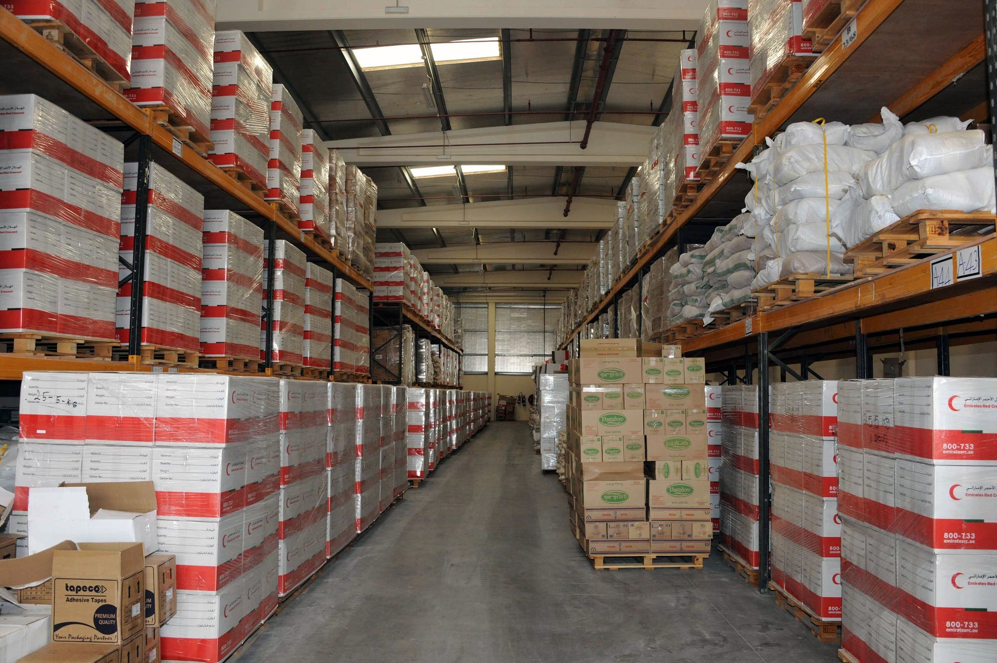 A handout image released by WAM on March 30, 2016 shows boxes of humanitarian aid stacked at a warehouse near the Emirates Red Crescent headquarters in Abu Dhabi, ahead of being transported residents in the war-torn Libyan city of Benghazi. (AFP)