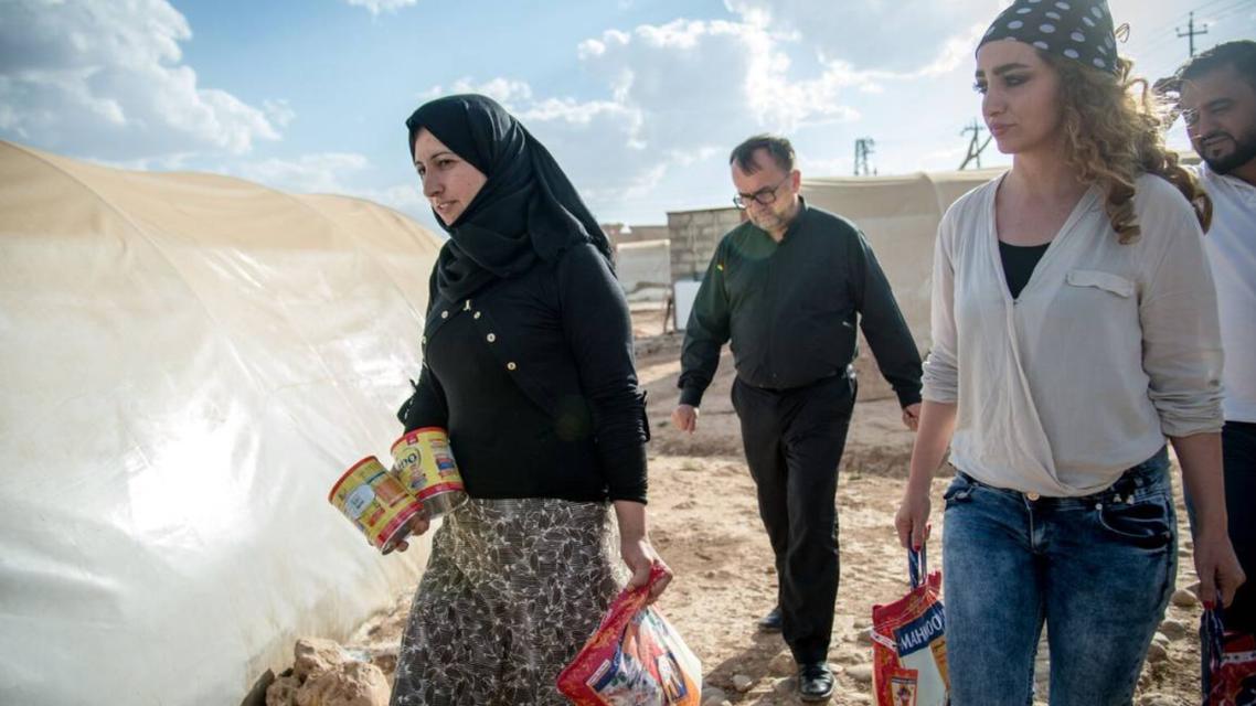 French priest Patrick Desbois (C) visits a refugee camp in Dahuk, Iraq in an undated photo. Credit Yahad In-Unum/Kate Kornberg reuters foundatiton