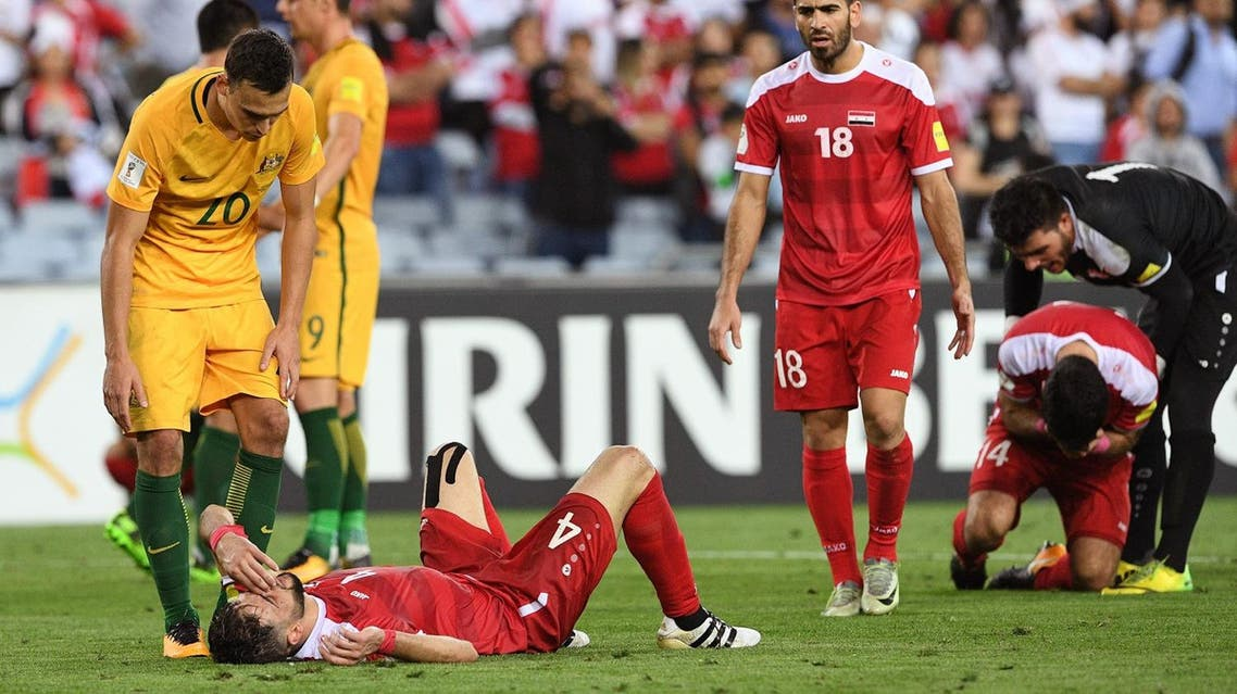 Trent Sainsbury of Australia (L) consoles Syrian Jehad Al Baour (2/L) after Australia defeated Syria in their 2018 World Cup football qualifying match played in Sydney on October 10, 2017. (AFP)