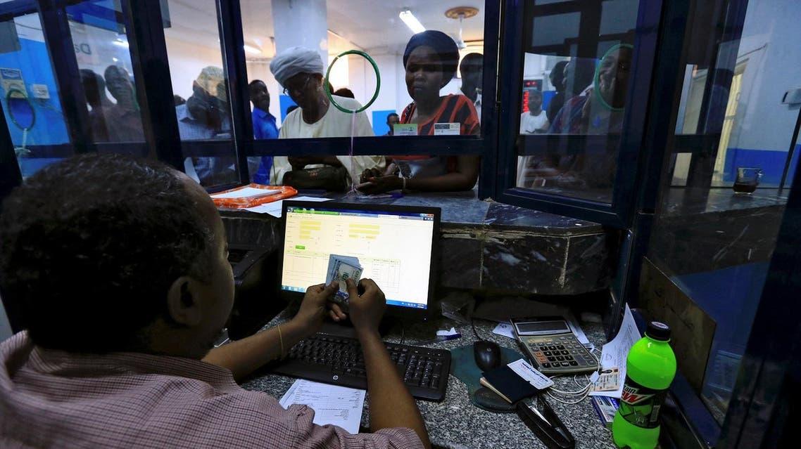 A cashier counts US Dollars as people wait to receive money inside Bab Al-Mandab Exchange transfer money bureau in Khartoum, Sudan October 7, 2017. REUTERS/Mohamed Nureldin Abdallah