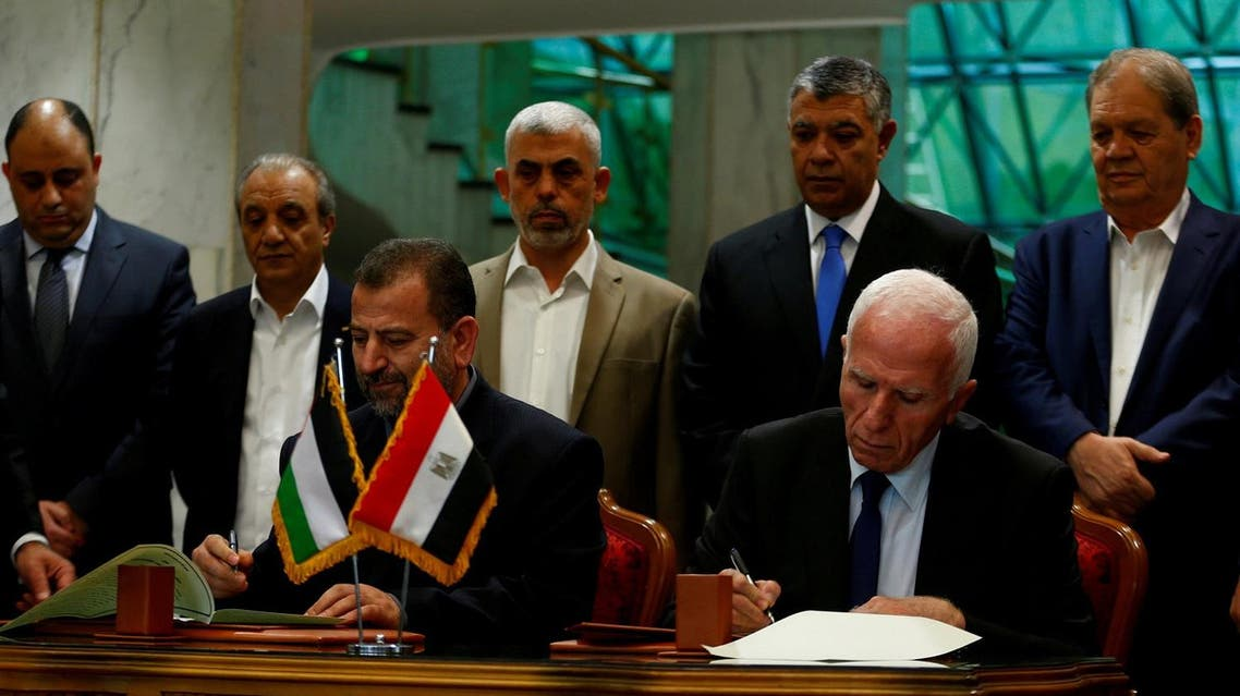 Head of Hamas delegation Saleh Arouri and Fatah leader Azzam Ahmad sign a reconciliation deal in Cairo, on October 12, 2017. (Reuters)
