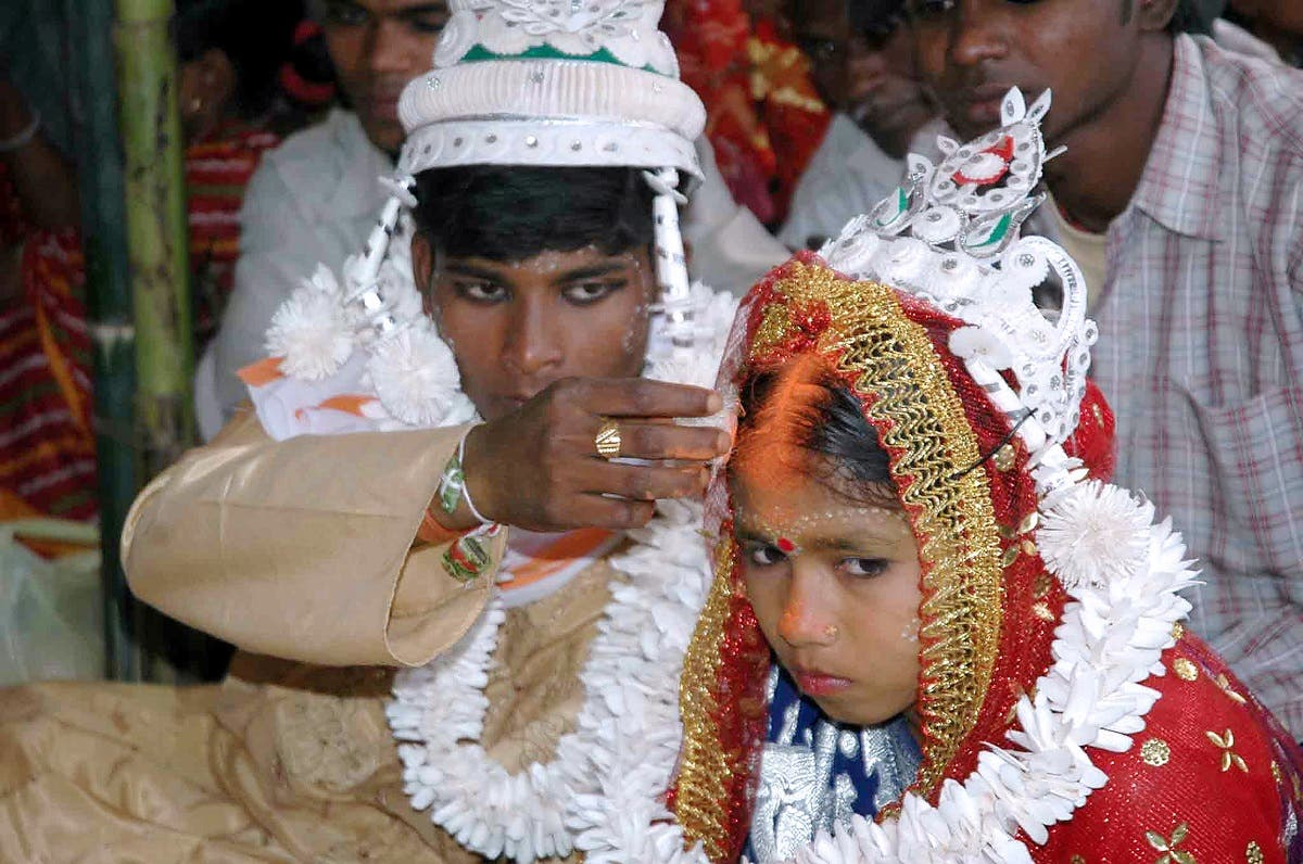 An Indian groom puts vermilion, the holy mark belived the as sign of hindu marriage, on the forehead of his underage bride during a mass marriage programme in the village of Malda, some 360 Kms. northeast of Kolkata, 02 March 2006. (AFP)